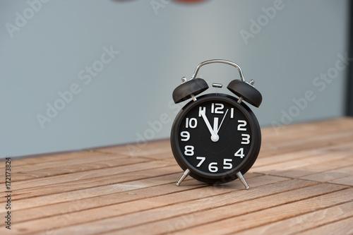 Retro Alarm Clock With Five Minutes To Twelve O Clock Stock Photo