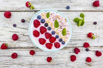 A bowl of healthy and delicious smoothie with grains and fresh berry fruit.