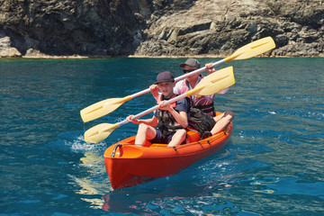 Boat kayaking near cliffs on a sunny day. Kayaking in a quiet bay. Amazing views. Travel, sports concept. Lifestyle. A happy family.