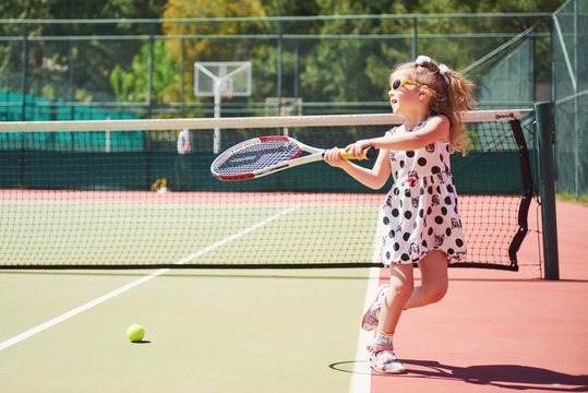 cute little girl playing tennis on the tennis court outside