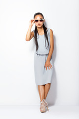 Young beautiful Asian woman in summer grey clothes and sunglasses