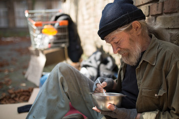 Close up view of tramp sitting by the brick wall, eating. Homeless man with his belongings living in the street.