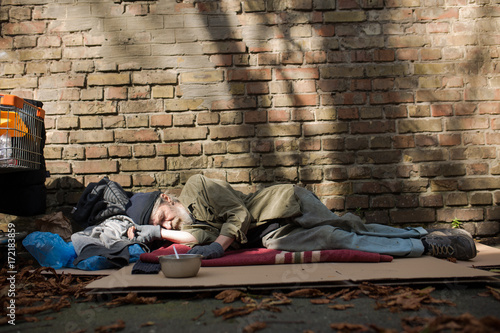 b5c7f59ece View of homeless man sleeping on cardboard on the ground. Diificult life of  a tramp with no home and money.