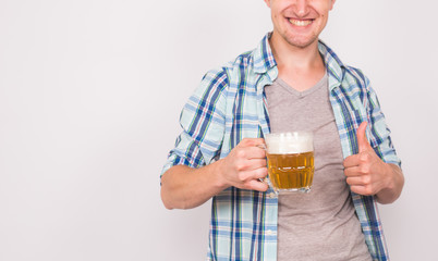 Close up of young man holding beer mug and showing thumbs up