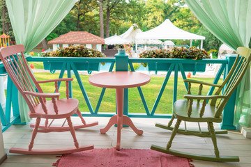 Pink and green wooden rocking chairs and table on porch or balcony. Two relaxing armchairs on porch of luxury hotel. Empty cafe with rocking chairs and table on summer  terrace outdoor, free space