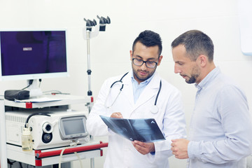 Patient and doctor looking at knee x-ray result in clinical office