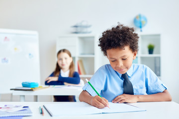 Little boy with pencil drawing or writing in notebook during lesson with schoolgirl on background