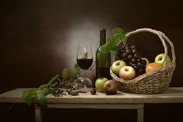 Still Life image of Fresh grapes and wine bottle in the brown basket with glass of wine and and fruits all put on wooden plank and green leaf