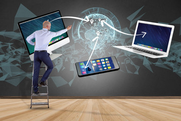 Businessman in front of a wall with Computer and devices displayed on a futuristic interface with interantional network - Multimedia and technology concept