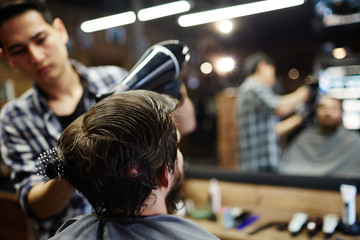 Hairdresser client having his hair dried with hair-dryer and styled with hairbrush