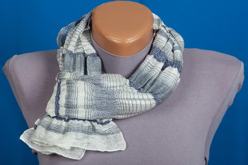 Gray scarf on mannequin isolated on blue background