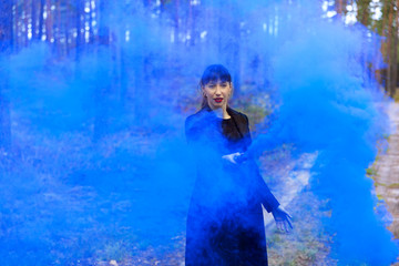 Young woman in forest having fun with blue smoke grenade, bomb