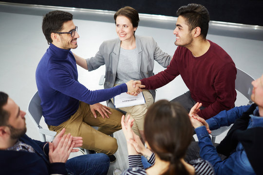 Happy men handshaking with helpful psychologist and applauding colleagues near by