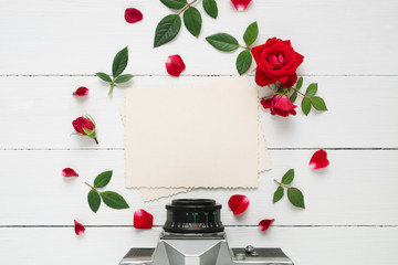 Retro empty photo frame for the inside, retro camera  and red rose flowers on white background. Flat lay, top view.
