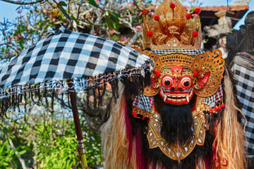 Rangda Mask under red umbrella in temple - traditional spirit of Bali at ceremony Melasti before Balinese New Year and silence day Nyepi Holidays, festivals, rituals, art, culture of Indonesian people