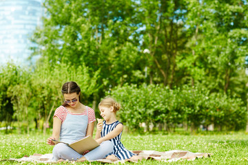Young woman and her daughter reading book of tales on green lawn on summer day