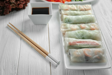 Plate with fresh spring rolls in rice paper on wooden table