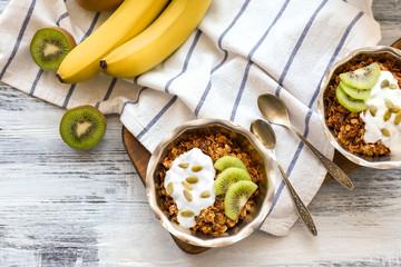Tasty dessert with yogurt in bowls on table