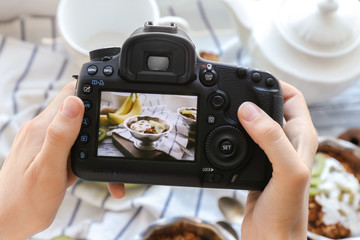 Young woman taking photo of delicious dessert in bowl with professional camera