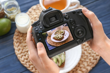 Young woman taking photo of delicious toasts with professional camera