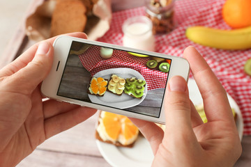 Young woman taking photo of delicious toasts with mobile phone