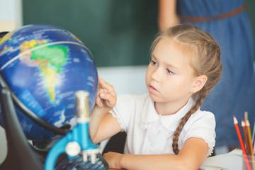 Schoolgirl looking at globe in school classroom