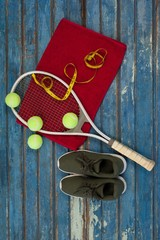 Overhead view of tennis equipment and tape measure on napkin by
