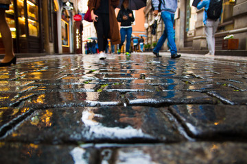 People walking on wet paving stones in rainy day in old town of Prague
