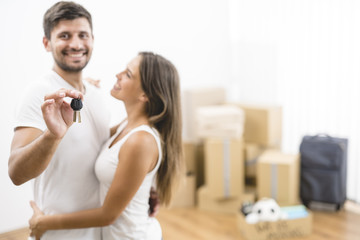 The couple hold keys on the background of the carton boxes