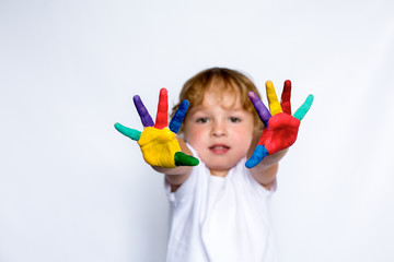 Happy little boy with colored hands on a white background, young artist, white t shirt model