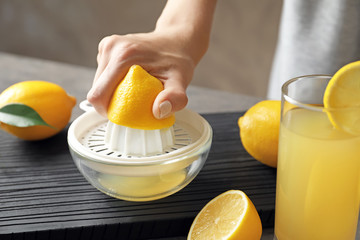 Woman squeezing lemon juice in kitchen
