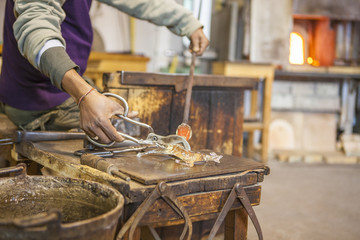 Midsection of glassblower working in workshop