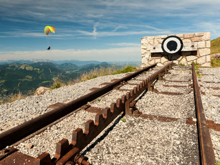 Endpoint of a rack railway on the top of a mountain with a paraglider in the background