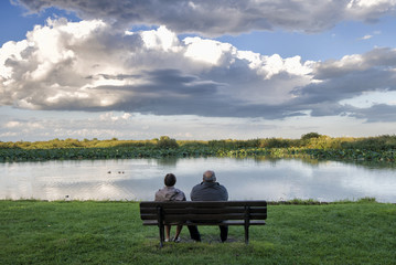 senior couple sitting over a bench in front of a pond at sunset