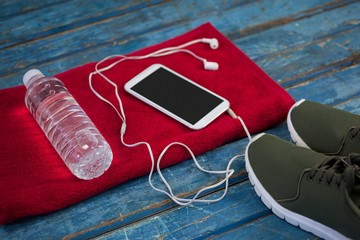 High angle view of water bottle with mobile phone and in-ear