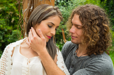 Happy couple in love at outdoors and smiling, man with curly hair touching the face of her girlfriend in a patio backyard background