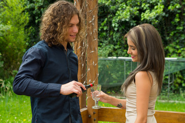 Happy couple in love at outdoors wearing casual clothes, woman holding a glass of wine while his boyfriend is serving the wine, in a patio backyard background