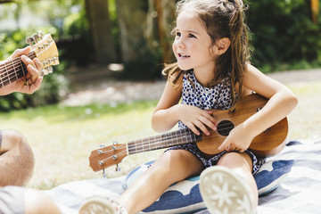 Young pretty girl playing with guitar at picnic in the park