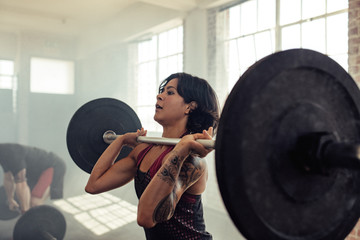 Woman doing front squats with barbells