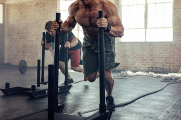 Muscular man doing prowler sled training at gym