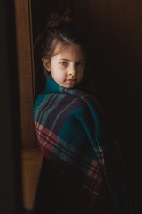 Portrait of young girl wrapped in a plaid blanket, looking at camera