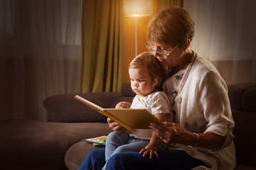 Grandmother reading a tale to her baby granddaughter. Family Reading Leisure
