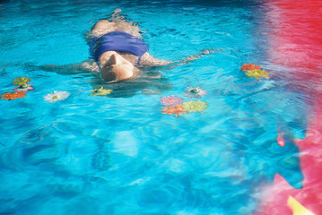 girl floating in pool with light leak effect on film