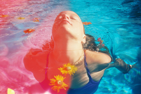 light leaked photo of girl swimming with colorful flowers in pool