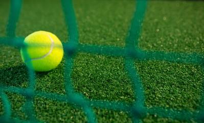 Close up of tennis ball seen through net