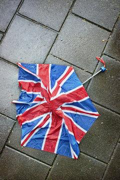 A broken umbrella  on the pavement