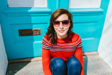 Portrait of young woman smiling by front door