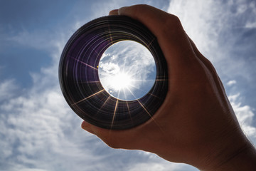 View through spyglass lens to the sun shining in the sky