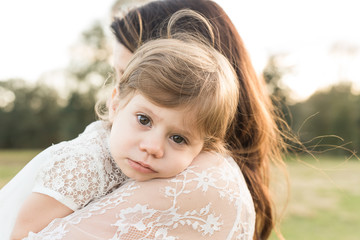 A Girl Resting Her Head On Her Mother's Shoulder