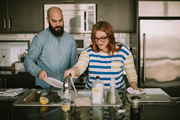 A Young Couple Does Dishes Together in Their Kitchen